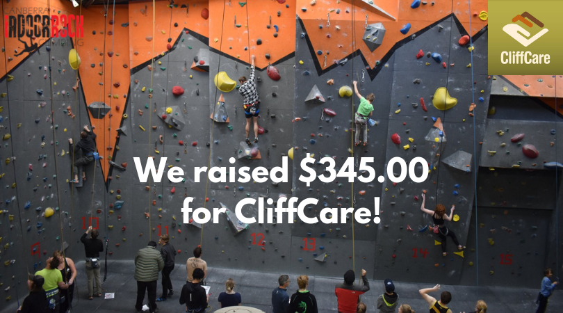 "A wide shot photo of the Mitchell gym during the competition, with four climbers visible on the wall and a large crowd observing. Image text reads: ""We raised $345.00 for CliffCare!"""