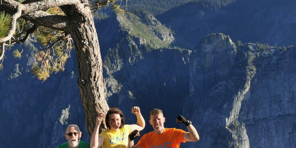 Peter, Cait, and Greg hold up fists and smile as they stand on the summit of El Cap together after topping out on the Nose Route. They stand beside a lone pine tree, and are all wearing Climbers Against Cancer t-shirts.